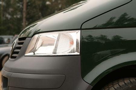 Close-up of green bus head light.