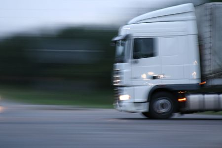 White truck on extreme high speed. Motion blur, shot on evening. photo