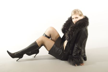 Blonde girl sitting on floor in a leather with fur jacket, leather skirt and knee-boots. Stock Photo