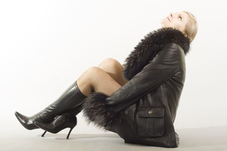 Blonde girl sitting on floor in a leather with fur jacket. photo