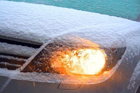 front bumper: Illuminated headlight at snowy weather.