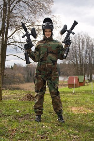 Girl-winner in camouflage posing with two guns. photo