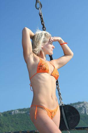 Blond girl in bikini posing on yacht. photo