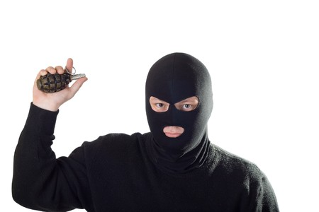 Terrorist in black mask with grenade. Isolated on white. photo