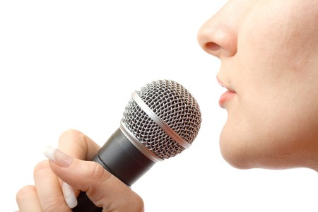 Caucasian girl singing with microphone. photo