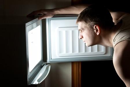 Hungry man opening fridge.