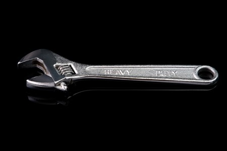 Adjustable chrome wrench. Isolated on black with reflection. photo