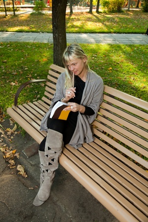 Young woman reading book with pencil in hand on a bench at an autumn park. photo