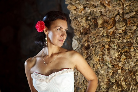 Brunette girl`s portret on antique stone wall background.