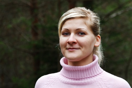 Young blond woman in sweater portrait in forest.