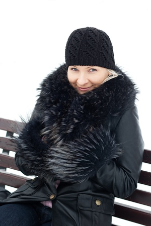 Young blond woman outdoor winter portrait on bench. photo