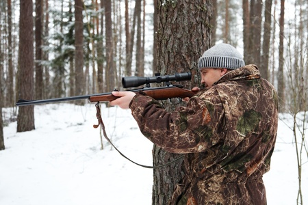 hunting rifle: Hunter in camouflage aiming with sniper rifle at winter forest.