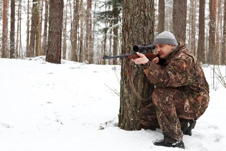 L'homme en tenue de camouflage visant à fusil de sniper à la forêt d'hiver.
