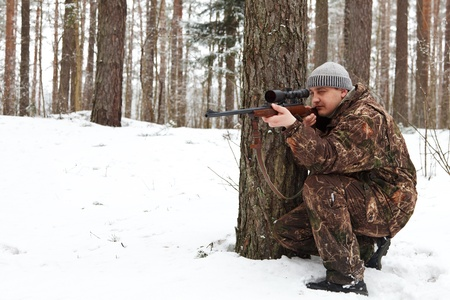 sniper rifle: Man in camouflage aiming with sniper rifle at winter forest.