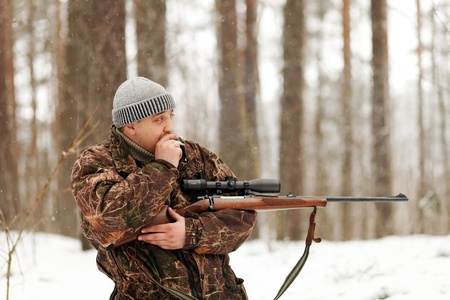 Smoking huter with rifle at winter forest. photo