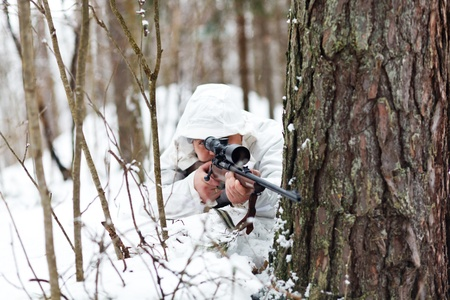 Soldier in white camouflage aiming with sniper rifle at winter forest. Stock Photo