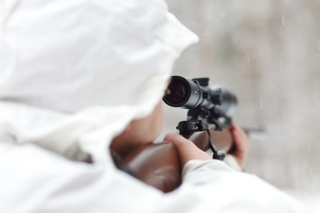 Soldier in white camouflage aiming with sniper rifle at winter forest. DOF photo