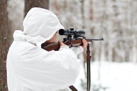 Soldier in white camouflage aiming with sniper rifle at winter forest. photo