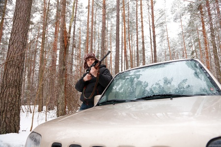 Man with sniper rifle and jeep in winter forest. Wide-angle shot. photo