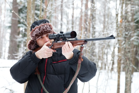 Hunter in a fur cap with ear flaps with sniper rifle in winter forest.