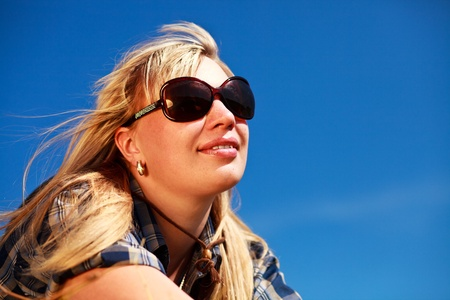 Blonde girl in checkered skirt and sunglasses portrait on blue sky background. photo
