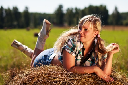 grass skirt: Country girl on straw bale. Stock Photo