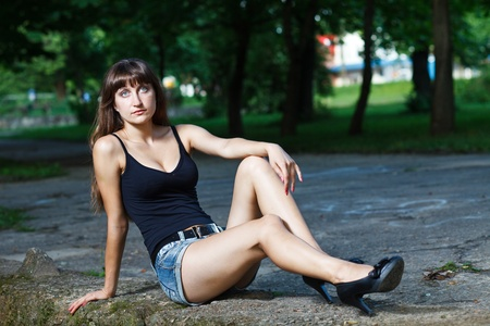 Caucasian long hair model in jeans shorts and black top sitting at flagstone. photo