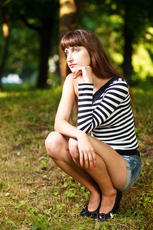 pantalones cortos: niña caucásica en el pensamiento despojado tapa y pantalones vaqueros. Foto de archivo