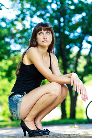 Caucasian long hair girl in jeans shorts and black top sitting at park. Stock Photo