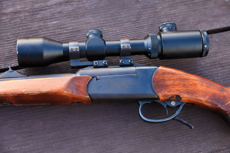 old rifle: Sniper rifle with optical sight on wooden table. Stock Photo