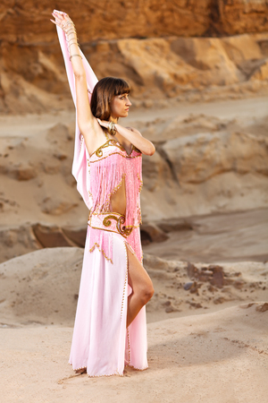 danseuse orientale: Danseuse du ventre sur fond de sable. Banque d'images