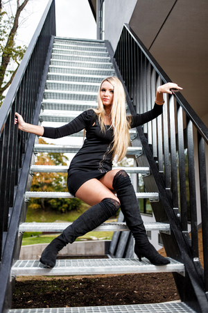 Blonde woman in black short dress sitting on staircase. Stock Photo