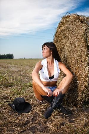 Sexy brunette assis près d'une botte de paille. Banque d'images