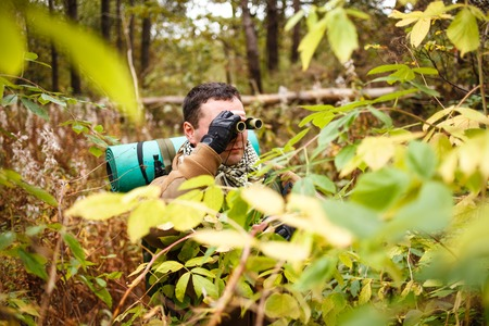 midlife: Caucasian man with binoculars at a jungle.