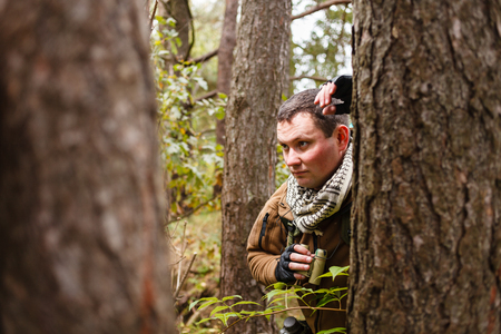 ranger: Caucasian man with binoculars at a forest.