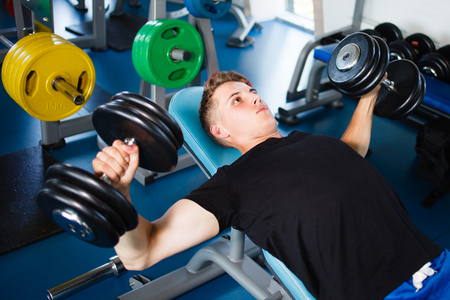 Exercising with dumbells at gym.