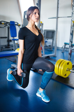 Long hail girl doing squats with a dumbbell. Stock Photo