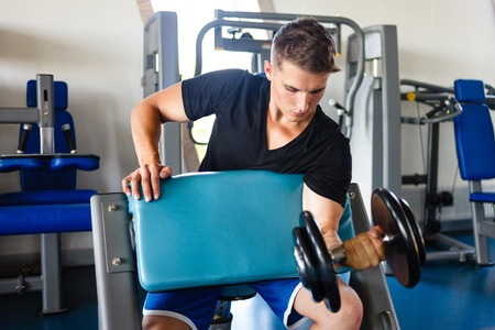 Young man biceps workout on a smitbench. Stock Photo