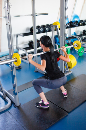 Long hail girl doing squats with a barbell.