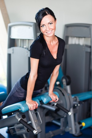 Smiling brunette in black t-shirt at gym. Stock Photo