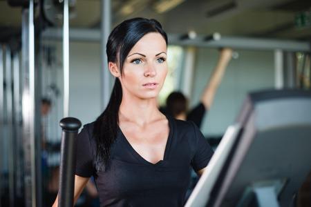 Running brunette in black t-shirt at gym.