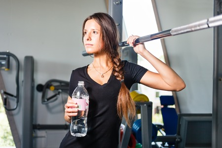 Girl with a water bottle in a gym. Stock Photo