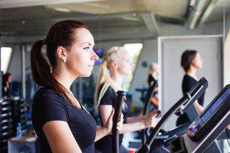 Three girls running on treadmills. Sport series