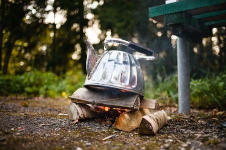 Camping iron kettle. Autumn photo on forest