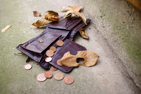 Old wallet with euro coins on concrete floor. Stock Photo