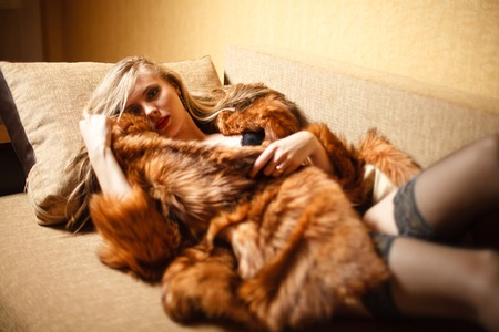Blond girl in fur and lingerie on sofa.
