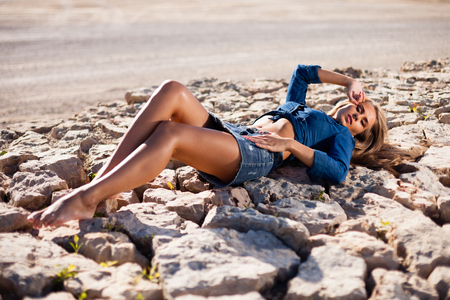 Caucasian long hair model in jeans shirt on rocks. Stock Photo