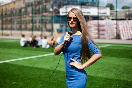 Pretty girl-reporterwith microphone on a stadium. Stock Photo