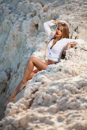 Caucasian long hair model posing in red bikini and white shirt on stones. Stock Photo