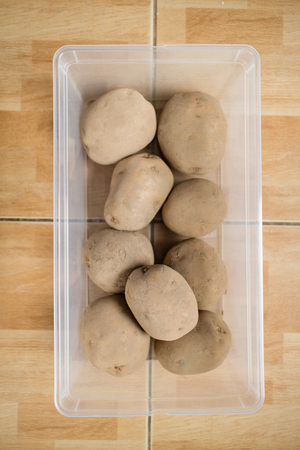 Raw potatoes in a plastic container on floor.